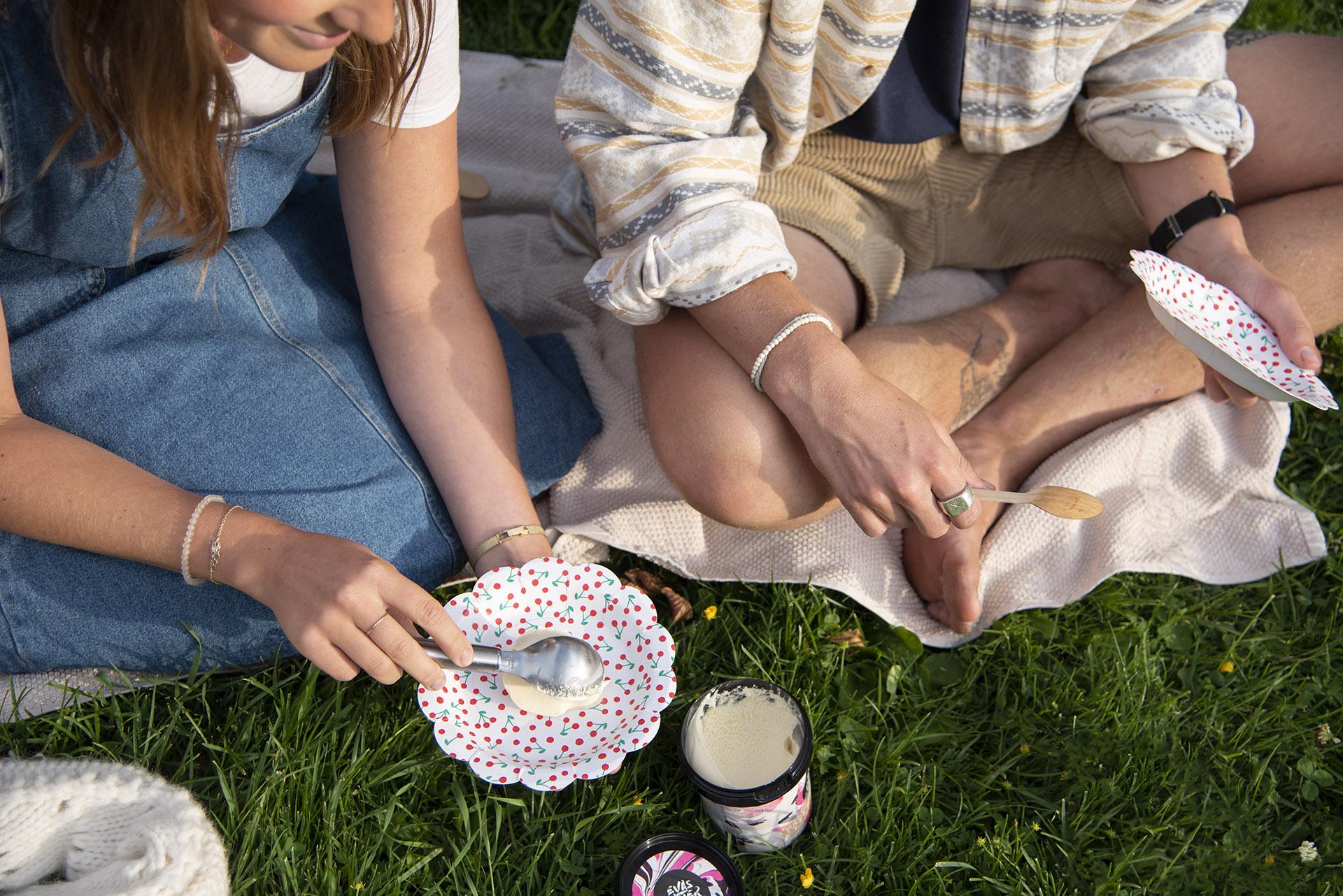 To personer spiser iskrem i parken.